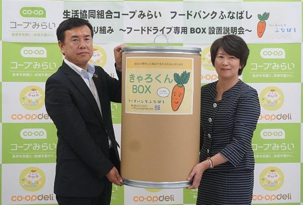「きゃろくんBOX」を手にするフードバンクふなばしの笹田明子代表(右)とコープみらい千葉県本部の鳥羽治明本部長(左)