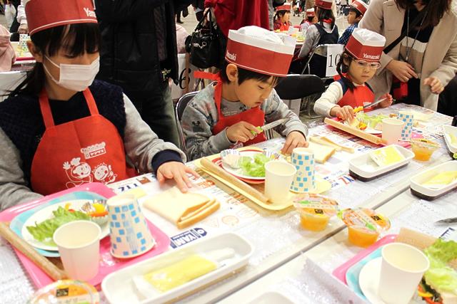 サンドイッチを作る子どもの写真