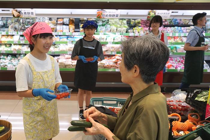 試食を提供しながらミニトマトを販売。子どもたちの呼びかけに組合員が足を止めていました(コープ南浦和店)