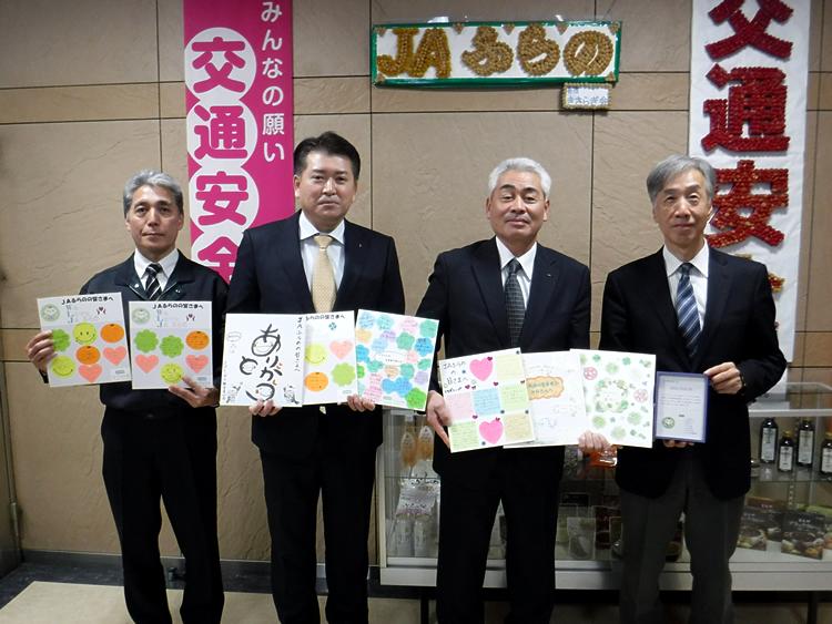 応援メッセージを手にする東藤部長、菊池常務、川上専務、赤松理事長の写真