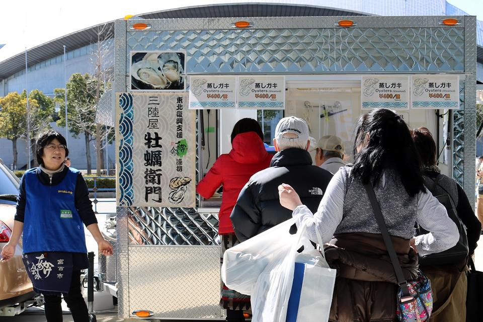 蒸しカキなどの海産物を販売している写真