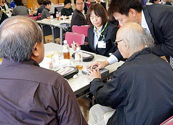 音声の再生機材を提供する、株式会社シナノケンシの社員がテーブルを回り、便利な操作方法を丁寧に教えていただいている様子の写真