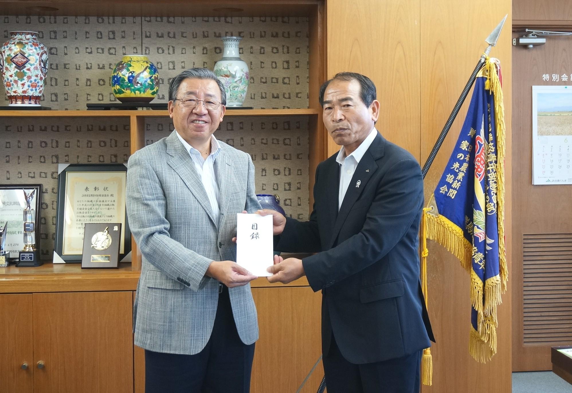 JA甘楽富岡の鷺坂代表理事組合長(右)に募金目録を贈呈する上原副理事長