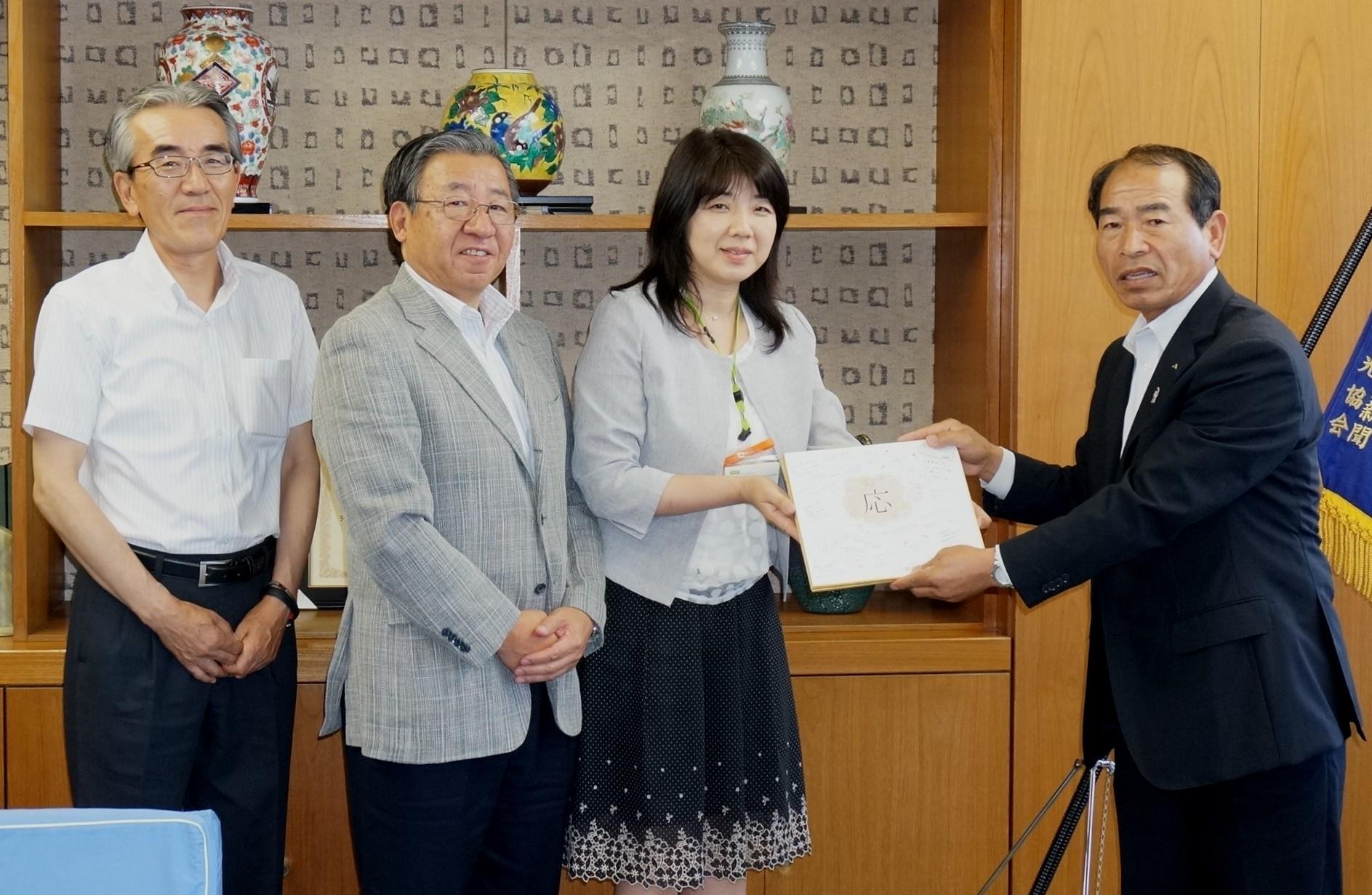鷺坂代表理事組合長に応援メッセージ色紙を贈呈する小倉組合員理事(右から2番目)、上原副理事長、コープぐんま梅澤理事長(左)