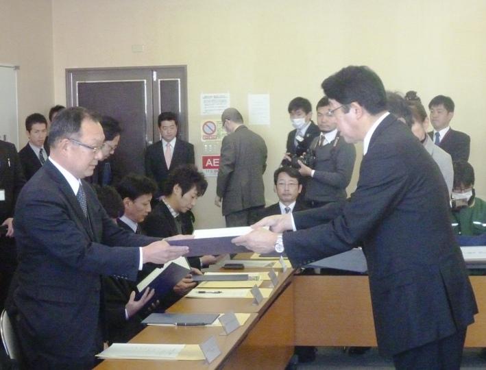 松崎市長(右)より石渡室長(左)に協定書が手渡されました。