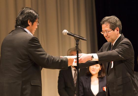 腎臓がんから現役復帰を果たした元プロレスラー、小橋建太さん(左)より、表彰状を授与されるコープみらいの大山克己人事教育執行役員